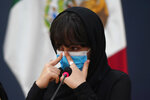 One of the original members of the Afghan all-girls robotics team, who have received threats from the Taliban, cries during a press conference after arriving at the Benito Juarez International Airport in Mexico City, Tuesday, Aug. 24, 2021. After extensive international efforts and coordination from a diverse group of volunteers to evacuate the team, the girls are now begging the international community to help get their family to safety with them. (AP Photo/Eduardo Verdugo)