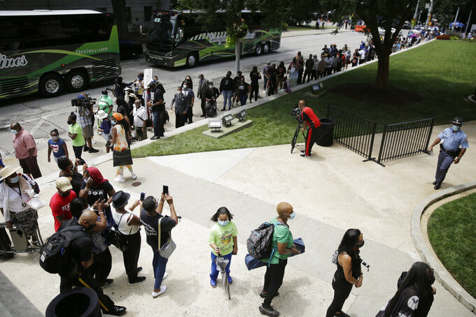 Mourners stand in line awaiting to pass by the casket of Rep. John Lewis as Lewis lies in repose at the state capital, Wednesday, July 29, 2020, in Atlanta. Lewis, who carried the struggle against racial discrimination from Southern battlegrounds of the 1960s to the halls of Congress, died Friday, July 17, 2020. (AP Photo/Brynn Anderson)