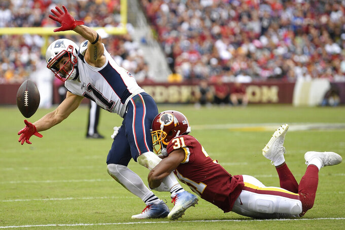 New England Patriots wide receiver Julian Edelman (11) misses the catch against Washington Redskins cornerback Fabian Moreau (31) during the first half of an NFL football game, Sunday, Oct. 6, 2019, in Washington. (AP Photo/Nick Wass)