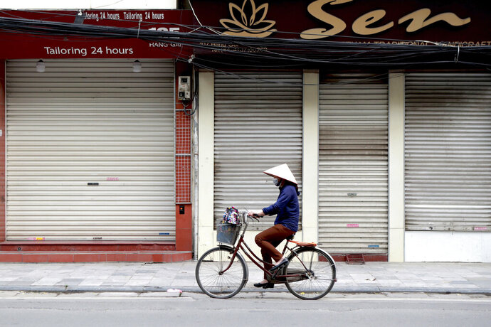 A woman cycles past closed shops in Hanoi, Vietnam, Friday, March 27, 2020. Vietnam's Prime Minister Nguyen Xuan Phuc has ordered to shut down non-essential business to curb the spread of COVID-19. The new coronavirus causes mild or moderate symptoms for most people, but for some, especially older adults and people with existing health problems, it can cause more severe illness or death. (AP Photo/Hau Dinh)
