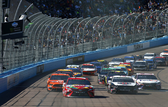 Kyle Busch (18) leads the field on a restart during the NASCAR Cup Series auto race at ISM Raceway, Sunday, March 10, 2019, in Avondale, Ariz. (AP Photo/Ralph Freso)
