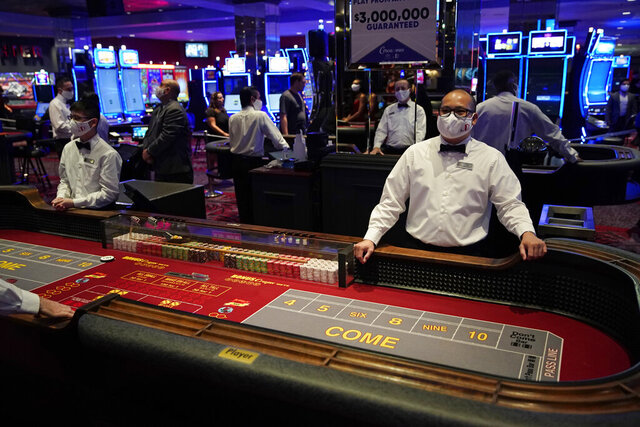 Dealers in masks wait for customers before the reopening of the D Las Vegas hotel and casino, Wednesday, June 3, 2020, in Las Vegas. Casinos were allowed to reopen on Thursday after temporary closures as a precaution against the coronavirus. (AP Photo/John Locher)