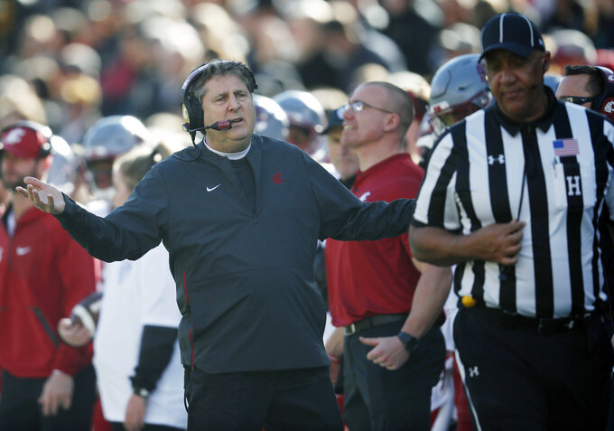 Washington State head coach Mike Leach, back, confers with head linesman Darryl Johnson in the first half of an NCAA college football game against Colorado Saturday, Nov. 10, 2018, in Boulder, Colo. (AP Photo/David Zalubowski)