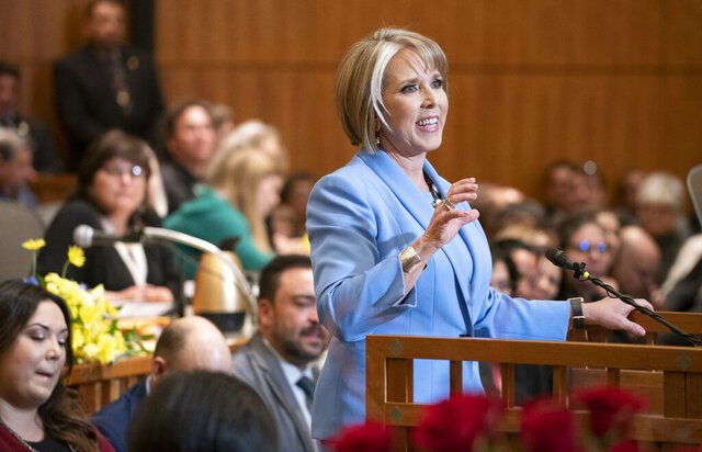 FILE - In this Jan. 15, 2019 file photo New Mexico Gov. Michelle Lujan Grisham gives her State of the State address during the opening of the New Mexico legislative session at the state Capitol in Santa Fe, N.M. New Mexico Democrats pushed forward a progressive agenda as the booming oil industry made headlines in 2019 with record revenues for the state's coffers. (AP Photo/Craig Fritz,File)