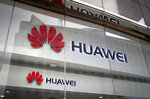 FILE - In this Jan. 29, 2019, file photo, the logos of Huawei are displayed at its retail shop window reflecting the Ministry of Foreign Affairs office in Beijing. China's Huawei is set to take the wraps off a new folding-screen phone, in a fresh bid for global dominance of the stagnating smartphone market. The company is expected on Sunday, Feb. 24, 2019 to unveil the new device, which can be used on superfast next-generation mobile networks due to come online in the coming years. (AP Photo/Andy Wong, File)