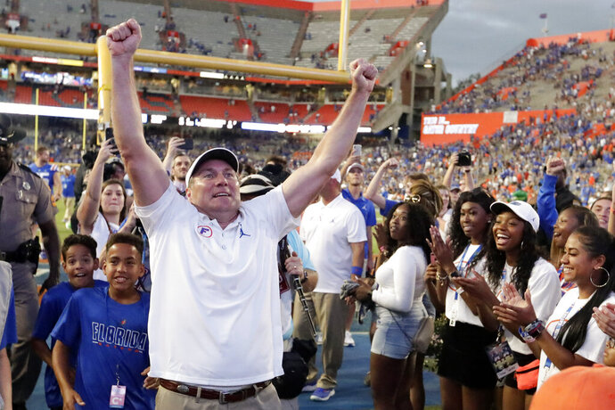 Florida head coach Dan Mullen celebrates in front of fans as he leaves the field after defeating Auburn in an NCAA college football game, Saturday, Oct. 5, 2019, in Gainesville, Fla. (AP Photo/John Raoux)