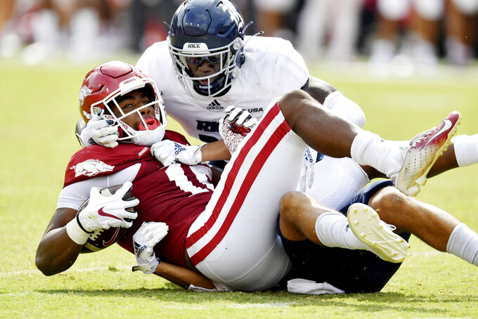 Arkansas receiver Treylon Burks (16) is tackled by Rice defender Keith CJ McCord II (20) during the second half of an NCAA college football game Saturday, Sept. 4, 2021, in Fayetteville, Ark. (AP Photo/Michael Woods)