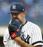 New York Yankees starting pitcher Jonathan Loaisiga (43) talks into his glove coming off the mound after allowing a run during the first inning of a baseball game against the Seattle Mariners, Wednesday, May 8, 2019, in New York. (AP Photo/Kathy Willens)
