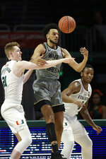 Wake Forest center Olivier Sarr, center, loses control of the ball as he is guarded by Miami forwards Sam Waardenburg (21) and Keith Stone (4) during the first half of an NCAA college basketball game, Saturday, Feb. 15, 2020, in Coral Gables, Fla. (AP Photo/Wilfredo Lee)