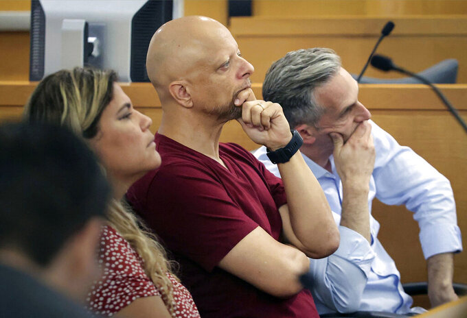 Champlain Towers South tenants Yadira Santo, from left to right, Paolo Longobardi and Oren Cytrynbaum listen closely as other residents share their grief and thoughts regarding the future of the site via Zoom, during a hearing, Wednesday, July 21, 2021, in Miami. Judge Michael Hanzman said victims and families who suffered losses in the collapse of the 12-story oceanfront Florida condominium will get a minimum of $150 million in compensation initially. (Carl Juste/Miami Herald via AP, Pool)