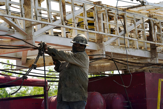 A well worker moves equipment at a site on Molly Rooke's ranch where an orphaned well was plugged, Tuesday, May 18, 2021, near Refugio, Texas. Oil and gas drilling began on the ranch in the 1920s and there were dozens of orphaned wells that needed to be plugged for safety and environmental protection. (AP Photo/Eric Gay)