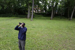Keith Russell, program manager of urban conservation at Audubon Pennsylvania, looks through binoculars while conducting a breeding bird census, at Wissahickon Valley Park Friday, June 5, 2020 in Philadelphia.  The viral video of a white woman targeting a Black bird watcher in New York's Central Park has renewed attention to how the great outdoors can often be far from great for Black people.  (AP Photo/Jacqueline Larma)