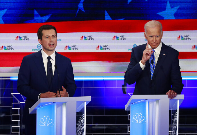 FILE - In this June 27, 2019, file photo, Democratic presidential candidate South Bend Mayor Pete Buttigieg, left, speaks as former vice president Joe Biden gestures during the Democratic primary debate hosted by NBC News at the Adrienne Arsht Center for the Performing Art in Miami. Biden and Buttigieg represent the generational poles of the crowded Democratic presidential primary. Biden is hoping Democratic voters see his decades of experience as the remedy for Trump's presidency. Buttigieg argues that the moment calls for the energy of a new generation. (AP Photo/Wilfredo Lee, File)
