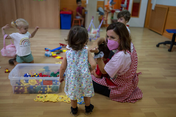A teacher wearing a face mask to protect against the spread of coronavirus  reacts with children in a class, at Vallehermoso school as the new school year begins, in Madrid, Spain, Monday, Sept. 6, 2021. Around 8 million children in Spain are set to start the new school year. (AP Photo/Manu Fernandez)