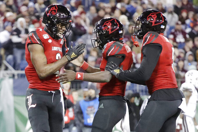 Louisville wide receiver Devante Peete, left, celebrates with quarterback Micale Cunningham, center, after they teamed up for a 24-yard pass completion for a touchdown against Mississippi State in the second half of the Music City Bowl NCAA college football game Monday, Dec. 30, 2019, in Nashville, Tenn. (AP Photo/Mark Humphrey)