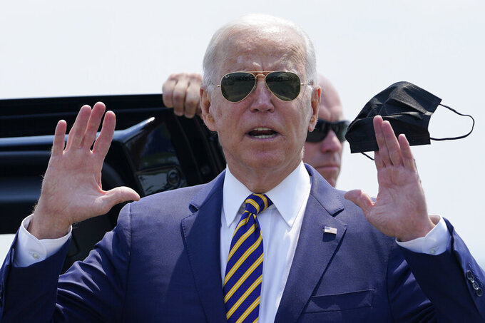 President Joe Biden holds a mask as he responds to a question as he arrives at Lehigh Valley International Airport in Allentown, Pa., Wednesday, July 28, 2021. Biden is in the area to visit the Lehigh Valley operations facility for Mack Trucks and advocate for government investments and clean energy as ways to strengthen U.S. manufacturing. (AP Photo/Susan Walsh)