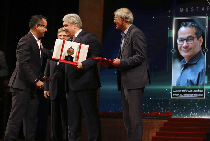 UCLA professor Ali Khademhosseini, left, is granted the Mustafa scientific prize by Vice President Sourena Sattari, center left, at a ceremony in Tehran, Iran, Monday, Nov. 11, 2019. Iran on Monday awarded a top prize in the study of science and technology to two U.S.-educated scientists --  Khademhosseini, for his work on the application of nanostructures in the treatment of disease and Umran Inan, a Turkish professor of electrical engineering at Stanford University. (AP Photo/Vahid Salemi)