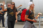 Members of the United States women's soccer team, winners of a fourth Women's World Cup, celebrate after arriving at Newark Liberty International Airport, Monday, July 8, 2019, in Newark, N.J. From left to right, Megan Rapinoe, Alex Morgan and Julie Ertz, holding the trophy. (AP Photo/Kathy Willens)