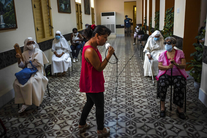 A woman sings for people who have just been inoculated with the Cuban Abdala COVID-19 vaccine as they wait in the observation area in Havana, Cuba, Wednesday, June 23, 2021. (AP Photo/Ramon Espinosa)