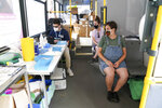 Festival goers Felicity Perry, foreground right and Sophie Edmondson wait to receive a COVID-19 vaccine on board a vaccination bus at the Latitude festival in Henham Park, in Southwold, England, Friday July 23, 2021. (Jacob King/PA via AP)