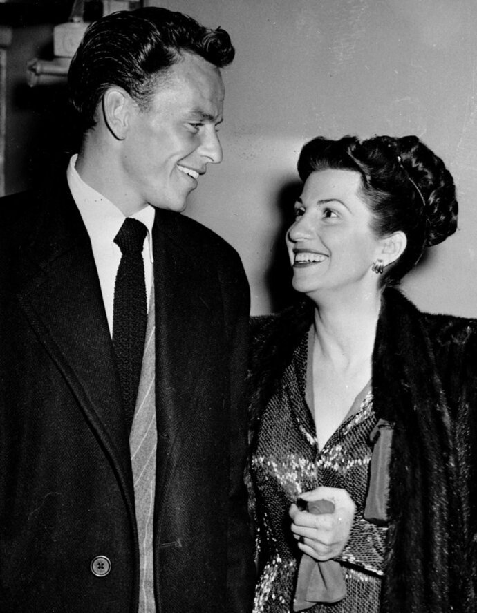 FILE - In this Oct. 23, 1946 file photo, singer Frank Sinatra and his wife Nancy smile broadly as they leave a Hollywood night club following a surprise meeting. Nancy Sinatra Sr., the childhood sweetheart of Frank Sinatra who became the first of his four wives and the mother of his three children, has died. She was 101. Her daughter, Nancy Sinatra Jr., tweeted that her mother died Friday, July 13, 2018.  (AP Photo/File)