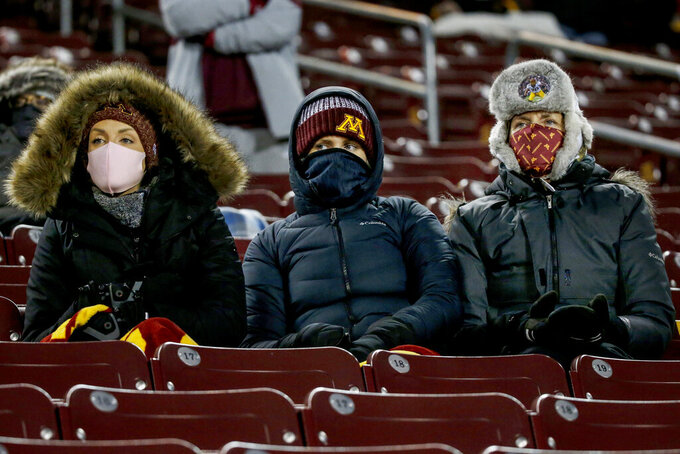 Minnesota fans watch the team play Michigan while social distancing and bundled up against the cold at an NCAA college football game Saturday, Oct. 24, 2020, in Minneapolis. Michigan won 49-24. (AP Photo/Bruce Kluckhohn)