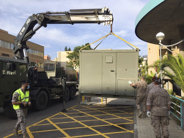 In this photo provided by the Spanish Ministry of Defence, soldiers install modules in the car park of the Hospital Clinico Universitario in Zaragoza, Spain, Tuesday Aug. 11, 2020. Spain's army is setting up a field hospital in Zaragoza as the northern city struggles to stop a new spike in cases of the coronavirus. The region of Aragon, home to Zaragoza, has led Spain over the past seven days with over 200 people hospitalized and  over 30 deaths from COVID-19. (MDE via AP)
