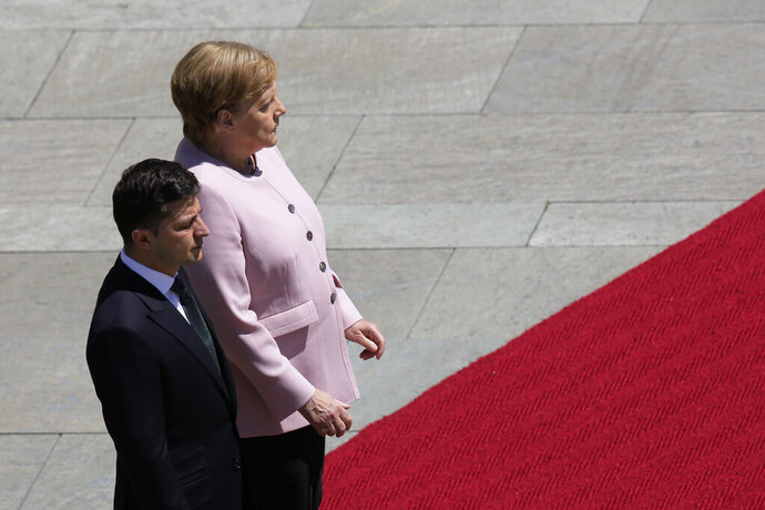 German Chancellor Angela Merkel, right, and Ukrainian President Volodymyr Zelenskiy, left, listen to the national anthems during the welcoming ceremony, prior to a meeting at the chancellery in Berlin, Germany, Tuesday, June 18, 2019. (AP Photo/Markus Schreiber)