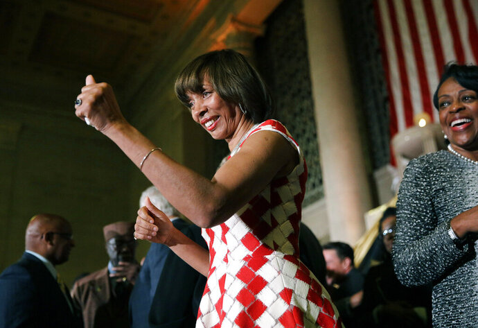 "FILE - In this Dec. 6, 2016 file photo, Baltimore Mayor Catherine Pugh gives a thumbs-up to supporters after her inauguration ceremony inside the War Memorial Building in Baltimore. The disgraced former mayor of Baltimore was charged Wednesday, Nov. 20, 2019, with fraud and tax evasion involving sales of her self-published children's books. An 11-count federal indictment accuses Pugh of using her ""Healthy Holly"" children's books to enrich herself, promote her political career and fund her run for mayor.  (AP Photo/Patrick Semansky, File)"