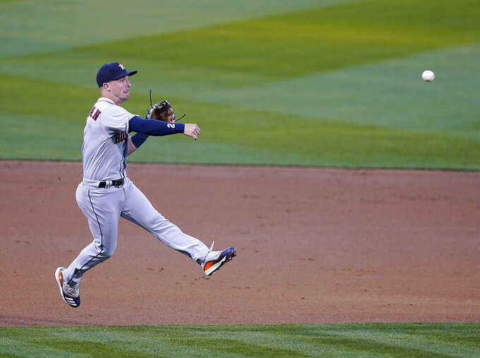Houston Astros third baseman Alex Bregman (2) throws to first base for an out against Oakland Athletics' Mark Canha in the first inning of an opening day baseball game Oakland, Calif., Thursday, April 1, 2021. (AP Photo/Tony Avelar)