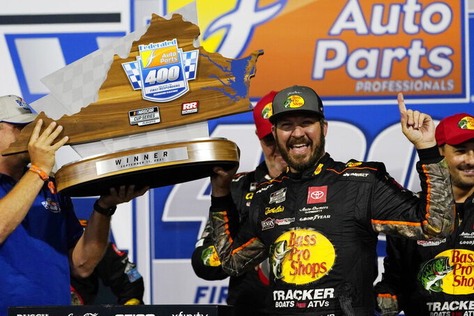 Martin Truex Jr., poses with the winners trophy as he celebrates winning the NASCAR Cup series auto race in Richmond, Va., Saturday, Sept. 11, 2021. (AP Photo/Steve Helber)