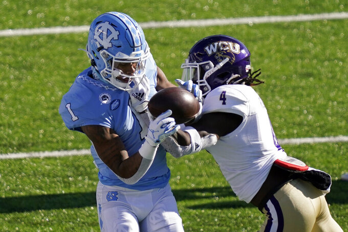 North Carolina wide receiver Khafre Brown (1) catches a pass while Western Carolina safety A.J. Rogers (4) defends during the first half of an NCAA college football game in Chapel Hill, N.C., Saturday, Dec. 5, 2020. (AP Photo/Gerry Broome)