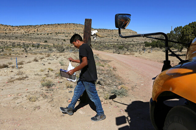 A student carries a math book delivered by school bus driver Kelly Maestas along his rural route outside Cuba, N.M., Oct. 19, 2020. The switch to remote learning in rural New Mexico has left some students profoundly isolated — cut off from others and the grid by sheer distance. The school system is sending school buses to students' far-flung homes to bring them assignments, meals and a little human contact. (AP Photo/Cedar Attanasio)