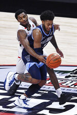 Hartford's Moses Flowers, left, fouls Villanova's Justin Moore in the first half of an NCAA college basketball game, Tuesday, Dec. 1, 2020, in Uncasville, Conn. (AP Photo/Jessica Hill)