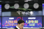 A currency trader watches the computer monitors near the screens showing the Korea Composite Stock Price Index (KOSPI), left, and the foreign exchange rate between U.S. dollar and South Korean won at the foreign exchange dealing room in Seoul, South Korea, Tuesday, March 31, 2020. Asian shares surged Tuesday after a rally in U.S. stocks, mostly spurred by health care companies' announcements of developments that could aid in the coronavirus outbreak. (AP Photo/Lee Jin-man)