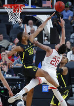 Oregon's Francis Okoro (33) ties to block a shot by Utah's Timmy Allen during the second half of an NCAA college basketball game in the quarterfinals of the Pac-12 men's tournament Thursday, March 14, 2019, in Las Vegas. (AP Photo/John Locher)