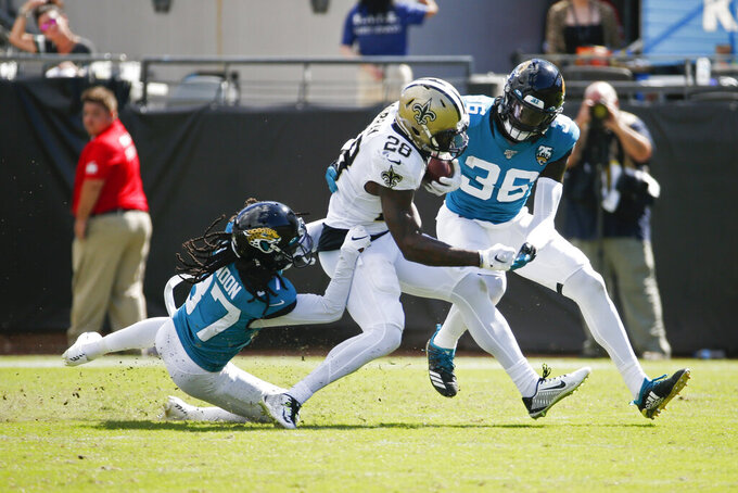Jacksonville Jaguars cornerback Tre Herndon, left, and defensive back Ronnie Harrison (36) tackle New Orleans Saints running back Latavius Murray (28) on a running play during the second half of an NFL football game, Sunday, Oct. 13, 2019, in Jacksonville, Fla. (AP Photo/Stephen B. Morton)