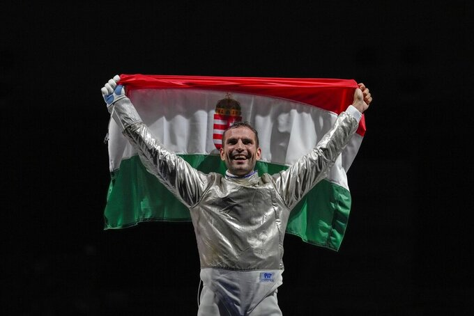Aron Szilagyi of Hungary celebrates with his national flag after winning the gold in the men's individual final Sabre competition at the 2020 Summer Olympics, Saturday, July 24, 2021, in Chiba, Japan. (AP Photo/Andrew Medichini)