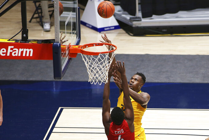 West Virginia forward Oscar Tshiebwe (34) shoots while defended by Richmond forward Nathan Cayo (4) during the first half of an NCAA college basketball game Sunday, Dec. 13, 2020, in Morgantown, W.Va. (AP Photo/Kathleen Batten)