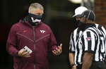 Virginia Tech head coach Justin Fuente talks with officials Gary Patterson and Terrence Ramsey prior to the Hokies' NCAA college football game against North Carolina, Saturday, Oct. 10, 2020 at Kenan Stadium in Chapel Hill, N.C. (Robert Willett/The News & Observer via AP)