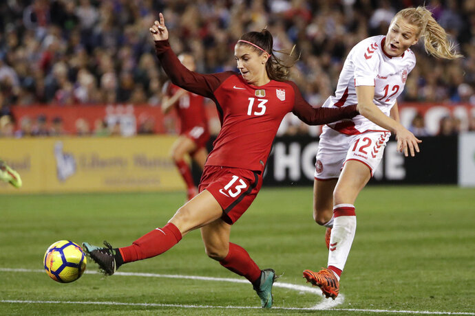 "FILE - In this Jan. 21, 2018, file photo, United States forward Alex Morgan, left, shoots on goal as Denmark forward Stine Larsen, right, defends during the second half of an international friendly soccer match in San Diego. She's already an internationally recognized soccer player with a World Cup title and an Olympic gold medal. She's also the author of a series of kids' books. Now you can add actor to Alex Morgan's resume. The U.S. national team forward makes her theatrical debut in a new feature ""Alex & Me"" about a young player who is inspired by Morgan. (AP Photo/Gregory Bull, File)"