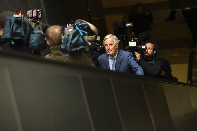European Union chief Brexit negotiator Michel Barnier, front, rides an escalator surrounded by the media on his way to a meeting at the Europa building in Brussels, Friday, Oct. 11, 2019. EU negotiator Michel Barnier says that he had a