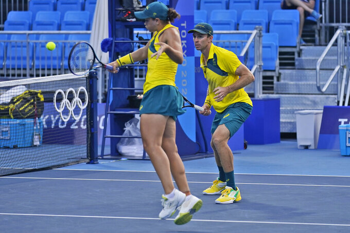 John Peers, of Australia, right, watches as Ashleigh Barty returns a shot during the first round of the mixed doubles tennis competition at the 2020 Summer Olympics, Wednesday, July 28, 2021, in Tokyo, Japan. (AP Photo/Seth Wenig)
