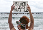 FILE - In this June 5, 2020, file photo, Shawna Ventimiglia from Manhattan Beach holds a sign in support of a local group of surfers during a traditional paddle out ceremony in Hermosa Beach in support of Black Lives Matter over the death of George Floyd in Los Angeles. Black Lives Matter has gone mainstream — and black activists are carefully assessing how they should respond. (AP Photo/Richard Vogel, File)
