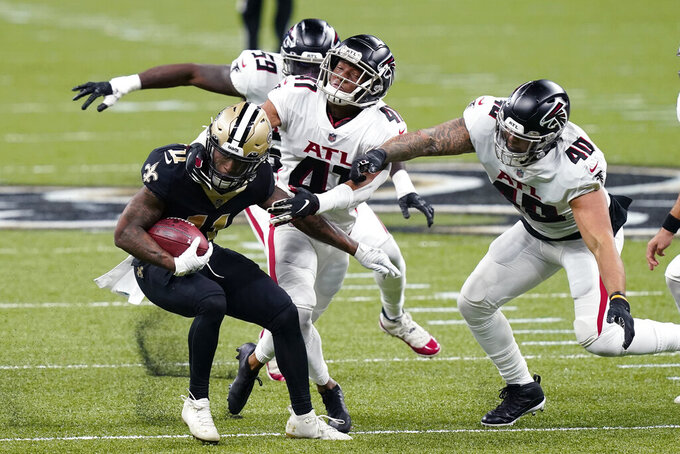New Orleans Saints Deonte Harris (11) returns a punt against Atlanta Falcons Sharrod Neasman (41), Keith Smith (40) and LaRoy Reynolds (59) in the first half of an NFL football game in New Orleans, Sunday, Nov. 22, 2020. (AP Photo/Butch Dill)