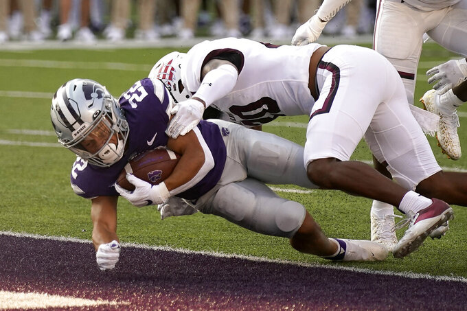 Kansas State running back Deuce Vaughn (22) falls into the end zone to score a touchdown as he is tackled by Southern Illinois cornerback David Miller (20) during the first half of an NCAA college football game against Southern Illinois, Saturday, Sept. 11, 2021, in Manhattan, Kan. (AP Photo/Charlie Riedel)
