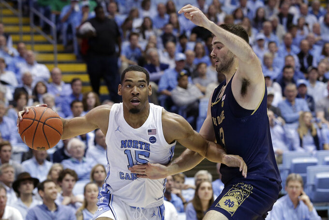 North Carolina forward Garrison Brooks (15) is pressured by Notre Dame forward John Mooney (33) during the first half of an NCAA college basketball game in Chapel Hill, N.C., Wednesday, Nov. 6, 2019. (AP Photo/Gerry Broome)