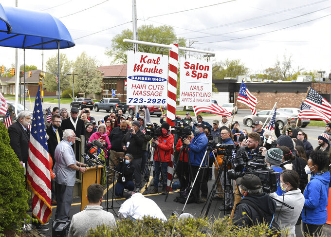 Karl Manke, owner of Karl Manke Barber Shop in Owosso, Mich., takes questions from reporters Monday, May 11, 2020, during a press conference outside his shop. Manke has defied the governor's order not to conduct business. (Matthew Dae Smith/Lansing State Journal via AP)