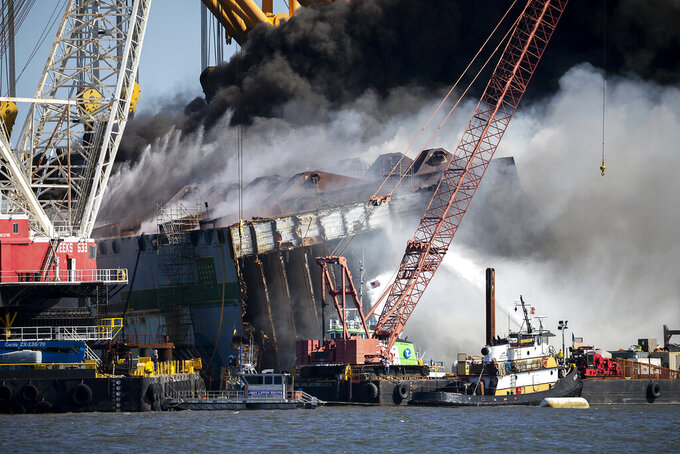 Firefighters spray water into the cut away mid-section of the cargo vessel Golden Ray, Friday, May 14, 2021, Brunswick, Ga. The final chunk of the cargo ship that capsized two years ago along the Georgia coast is awaiting removal from the water. The South Korean freighter Golden Ray overturned with 4,200 vehicles in its cargo decks in September 2019. Salvage crews have worked since November to cut the ship into eight giant sections and remove them one at a time. The multiagency command overseeing the ship's demolition said in a news release Monday, Sept. 27, 2021 that the seventh segment was loaded onto a barge and taken to a local dock over the weekend. (AP Photo/Stephen B. Morton)