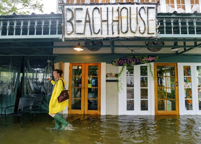 FILE - In this July 13, 2019, file photo Aimee Cutter, the owner of Beach House restaurant, walks through water surge from Lake Pontchartrain on Lakeshore Drive in Mandeville, La., ahead of Tropical Storm Barry. Months after a storm, fire or other disaster has struck, small businesses that have lost revenue due to the devastation may be able to get low-cost Small Business Administration loans. Financial help in the form of economic injury disaster loans are for companies even if they haven't suffered physical damage in a declared disaster area. These loans are separate from those made available to homeowners and businesses who need to rebuild or repair. (AP Photo/Matthew Hinton, File)